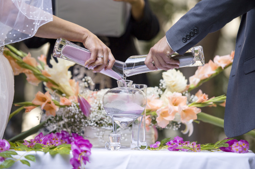 Two well-dressed people pour different colored liquids into the same glass as a commitment ceremony.